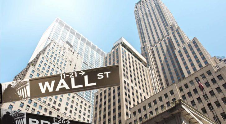 skyscraper buildings viewed from the ground with Wall Street street sign in the foreground