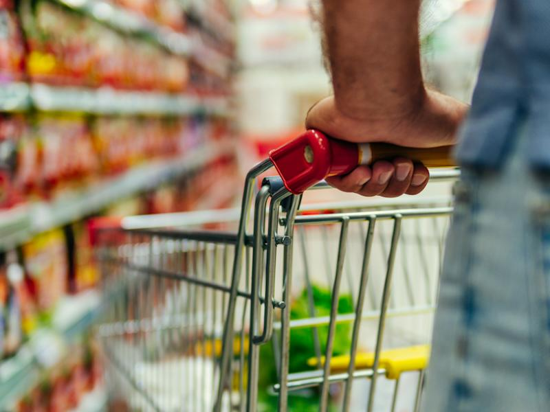Shopping cart in supermarket. Caucasian or latin man hands hold shopping trolley in supermarket aisle.