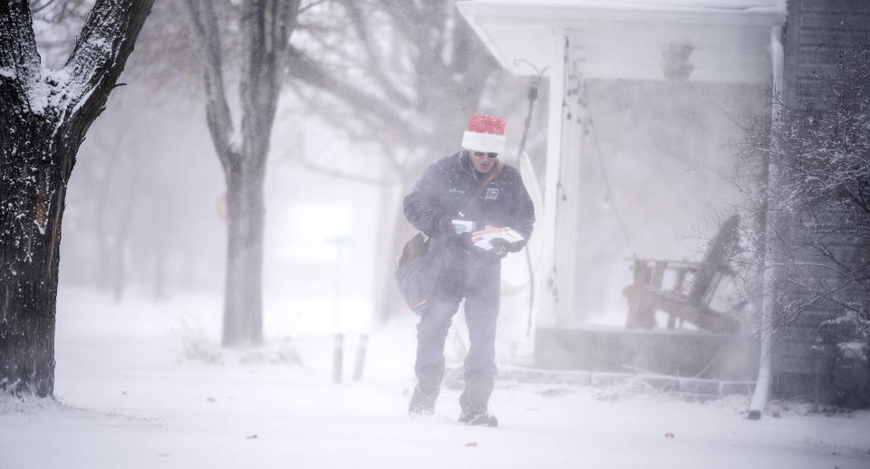 Mail carrier Dennis Niles braves the blowing snow as blizzard like conditions hit Osseo and the Twins Cites on Wednesday, Dec. 23, 2020 in Osseo, Minn. (Jerry Holt/Star Tribune via AP)
