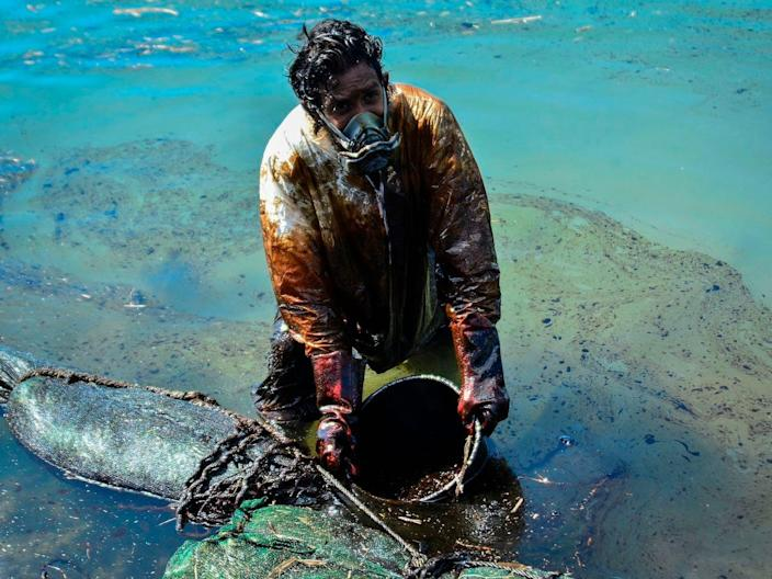 """A man scoops leaked oil from the vessel MV Wakashio, belonging to a Japanese company but Panamanian-flagged, that ran aground near Blue Bay Marine Park off the coast of south-east Mauritius on August 8, 2020. <p class=""""copyright"""">ean Aurelio PRUDENCE / L'Express Maurice / AFP</p>"""