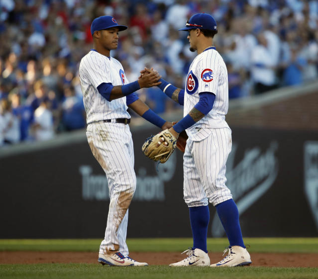 Chicago Cubs' Addison Russell, left, celebrates with teammate Javier Baez, right, after beating the Cincinnati Reds in a baseball game in Chicago, on Saturday, Sept. 15, 2018. The Cubs won the game 1-0. (AP Photo/Jeff Haynes)