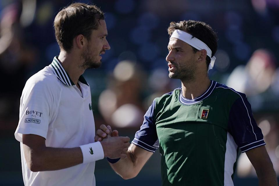 Grigor Dimitrov shakes hands with Daniil Medvedev after their match.