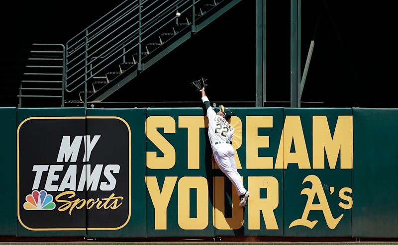 Oakland Athletics center fielder Ramon Laureano jumps to catch a fly ball hit by Toronto Blue Jays' Teoscar Hernandez during the second inning of a baseball game in Oakland, Calif., Sunday, April 21, 2019. (AP Photo/Jeff Chiu)