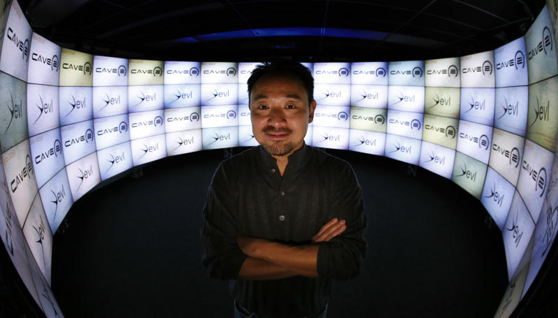 In this photo taken Thursday, Jan. 24, 2013, in Chicago, University of Illinois-Chicago computer scientist Jason Leigh, co-inventor of the CAVE2 virtual reality system, stands in the CAVE2's doorway where the system's 72 stereoscopic liquid crystal display panels encircles the viewer 320 degrees and creates a 3D environment that can take you to the bridge of the Starship Enterprise, a flyover the planet Mars, or through the blood vessels of the brain. (AP Photo/Charles Rex Arbogast)