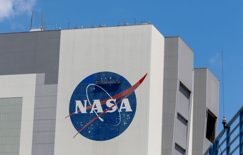 Workers pressure wash the logo of NASA on the Vehicle Assembly Building, in Cape Canaveral