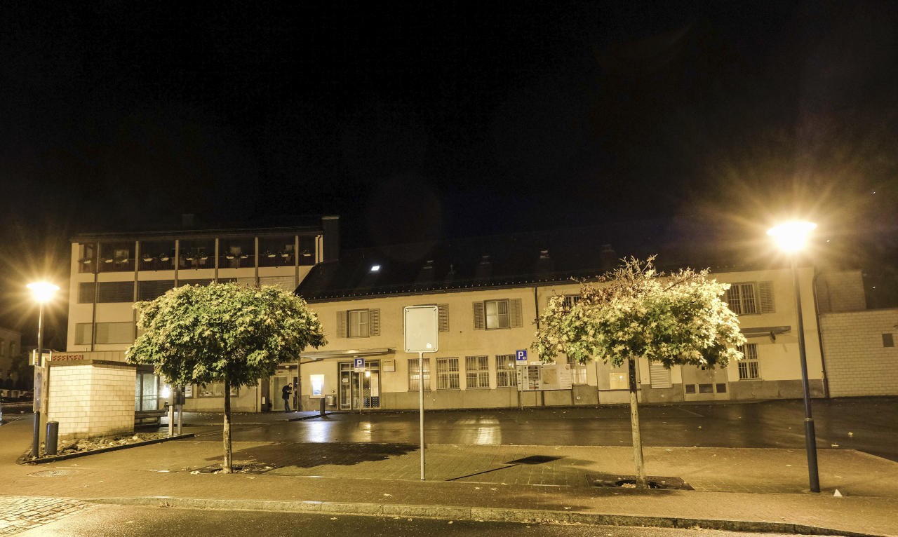 This photo shows a town square in Flums, Switzerland, Sunday, Oct. 22, 2017, after several were injured in an ax attack. Police believe the suspect attacked several people in the town square, then fled with a stolen car, which later was involved in an accident. The suspect continued on foot before attacking more people at a gas station shop, where he was arrested, police said. (Eddy Risch/Keystone via AP)