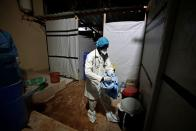 Professor Moussa Seydi, removes his personal protective equipment (PPE) after meeting his patients suffering from the coronavirus disease (COVID-19) at the infectious diseases department of the the University Hospital Fann, in Dakar