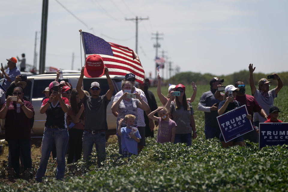 President Donald Trump supporters watch as the motorcade for Trump passes by en route to the Double Eagle Energy Oil Rig, Wednesday, July 29, 2020, in Midland, Texas. (AP Photo/Evan Vucci)