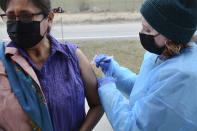 In this Thursday, April 29, 2021, photo, Sherry Cross Child, a Canadian resident of Stand Off, Alberta, receives a COVID-19 vaccine at the Piegan-Carway border crossing near Babb, Mont. The Blackfeet tribe in northern Montana gave out surplus vaccines in April to its First Nations relatives and others from across the border. (AP Photo/Iris Samuels)