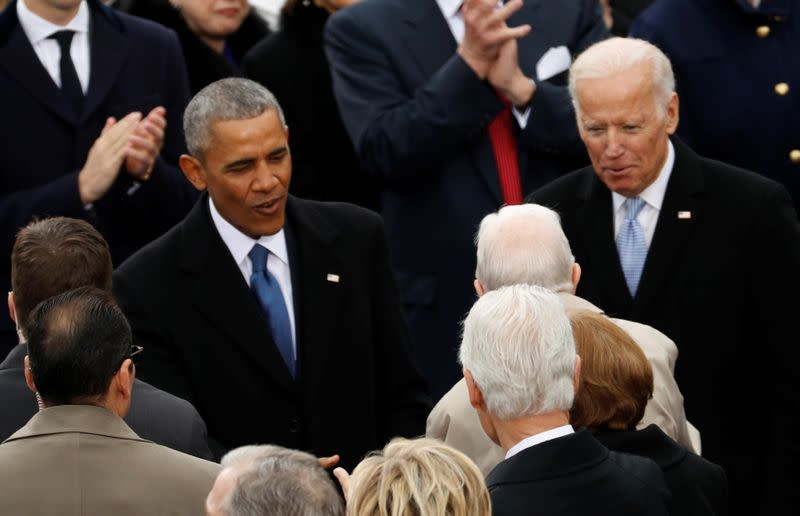 FILE PHOTO: U.S. President Barack Obama and Vice President Joe Biden talk to guests at the inauguration ceremonies swearing in Donald Trump as the 45th president of the United States on the West front of the U.S. Capitol in Washington