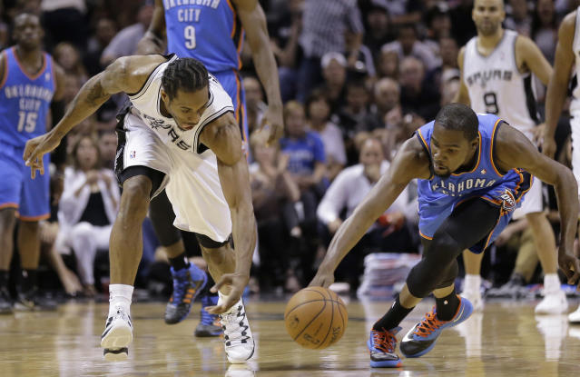 San Antonio Spurs' Kawhi Leonard, left, and Oklahoma City Thunder's Kevin Durant reach for the ball during the first half of Game 5 of the Western Conference finals NBA basketball playoff series, Thursday, May 29, 2014, in San Antonio. (AP Photo/Eric Gay)