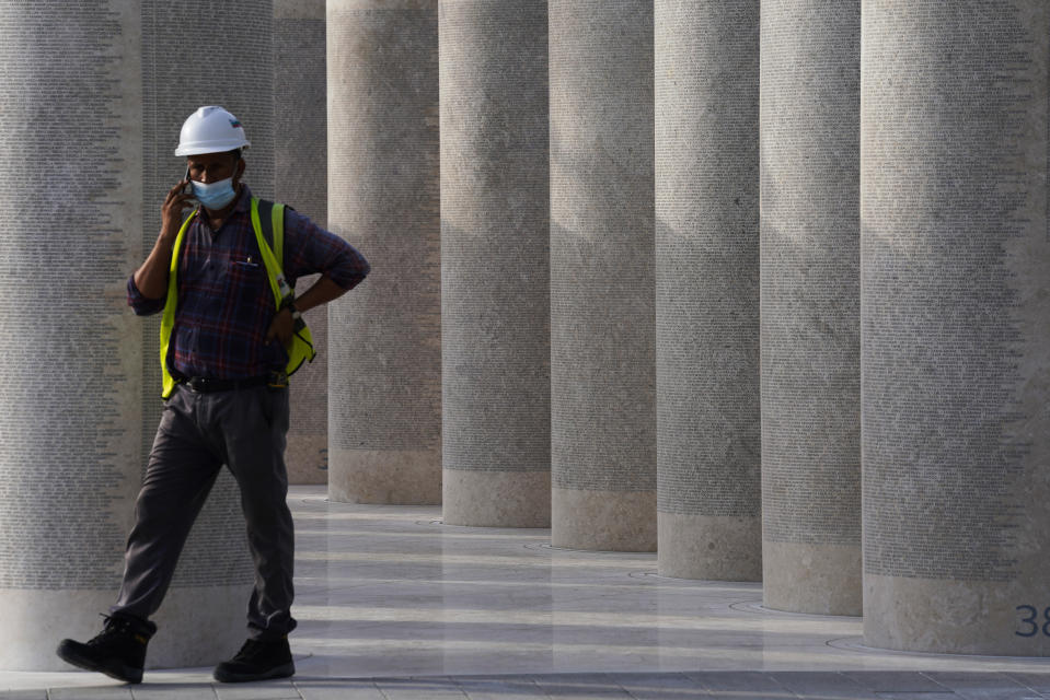 """A worker talks on the phone by an installation honoring the foreign laborers who built Expo 2020 in Dubai, United Arab Emirates, Sunday, Oct. 3, 2021. Dubai's Expo 2020 on Saturday, Oct. 2, 2021, offered conflicting figures for how many workers had been killed on site during construction of the massive world's fair, first saying five and then later three. In a later statement, Expo apologized and described the initial figure as a """"mistake."""" (AP Photo/Jon Gambrell)"""