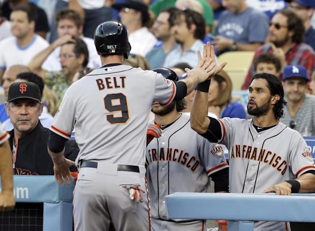 San Francisco Giants' Brandon Belt celebrates with teammates after scoring on a Hunter Pence base hit against the Los Angeles Dodgers in the first inning of a baseball game in Los Angeles Saturday, Sept. 14, 2013. (AP Photo/Reed Saxon)