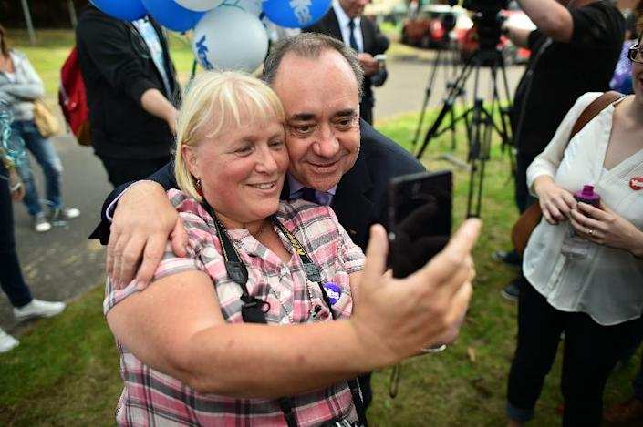 Scotland's First Minister Alex Salmond (R) poses for a selfie with a woman during a visit to a housing estate in Glasgow on September 13, 2014 (AFP Photo/Ben Stansall)