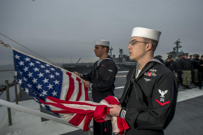 Logistics Specialist 3rd Class Logan Davidson, right, and Aviation Boatswain's Mate (Handling) Airman Recruit Gabriel Gonzalez, conduct morning colors on the flight deck aboard the aircraft carrier <em>USS George H.W. Bush</em> (CVN 77) on Dec. 1. The flag was flown at half-mast to honor the 41st president, the ship's namesake, who died on Friday. The ship is in port in Norfolk, Va., conducting routine training exercises to maintain carrier readiness. (Photo: Mass Communication Specialist 3rd Class Zachary P. Wickline/U.S. Navy via AP)