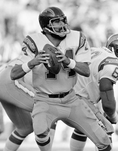 FILE - In this Dec. 27, 1982, file photo, San Diego Chargers quarterback Dan Fouts (14) looks downfield before releasing a pass against the Baltimore Colts during an NFL football game in San Diego. The biggest piece of San Diego's sports history is slowly being knocked down and ground to bits. Now the stadium is coming to an unceremonious end, leaving generations of fans feeling melancholy because, due to the coronavirus pandemic, they didn't get to say a proper goodbye to the place where they tailgated with gusto in the massive parking lot before cheering on the Chargers, Padres and Aztecs, or watched myriad other events and concerts. (AP Photo/Lenny Ignelzi, File)