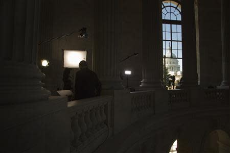 U.S. Senator Johnny Isakson (R-GA) (L) waits to go live for a network TV interview in the Russell Senate Office Building next to the U.S. Capitol in Washington, October 2, 2013. REUTERS/Jonathan Ernst
