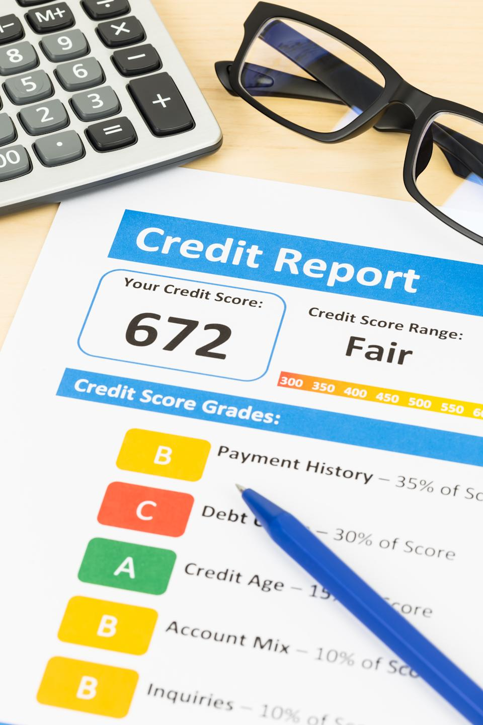 Fair credit score report with pen and calculator; document and the report are mocked-up