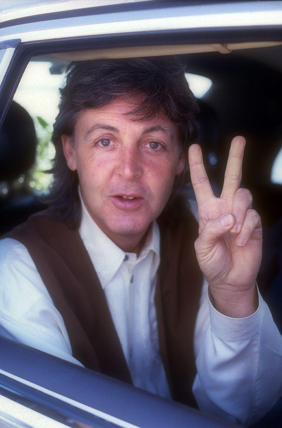 "<p>Paul McCartney does a peace sign in the back of a car in Amsterdam, Netherlands.</p><p>Other celebrity visitors this year:<span class=""redactor-invisible-space""> Diana Ross, David Bowie, Neil Young.<br></span></p>"