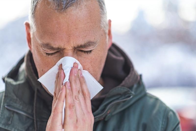 Man blowing his nose in the cold weather