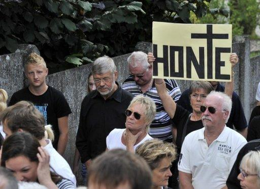 Protesters hold a banner reading 'Shame' during a protest outside a convent in Malonne