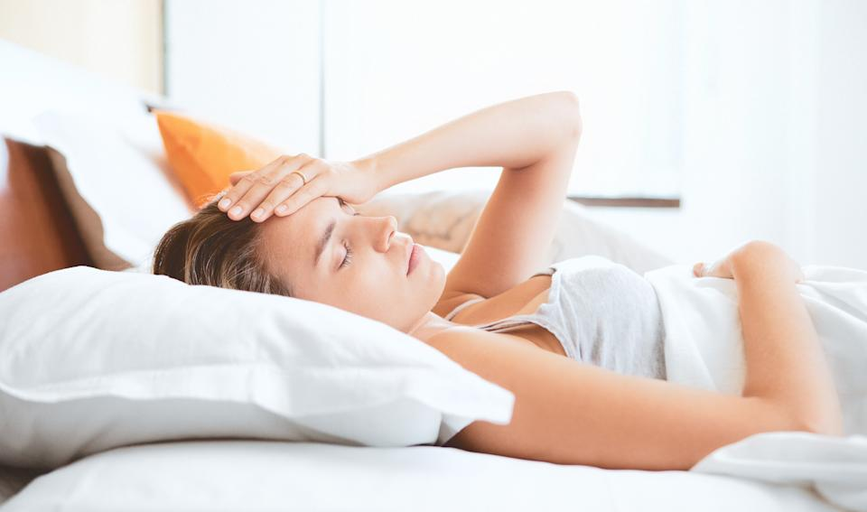 Young woman on bed, headache