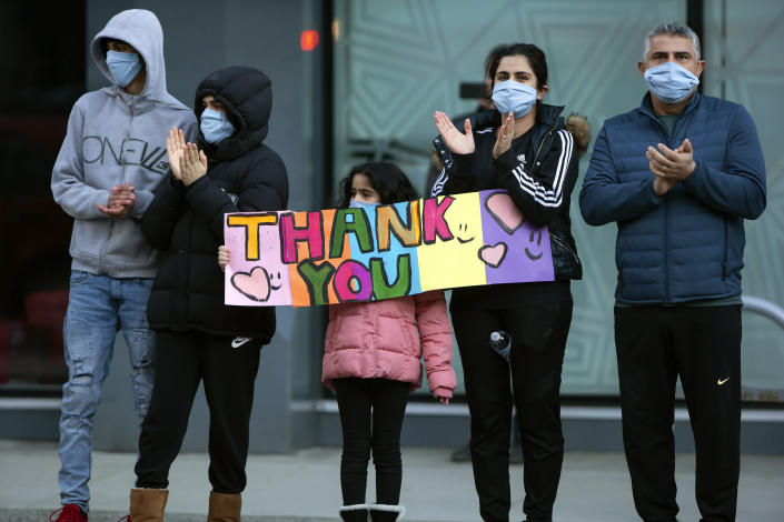 A family holds a sign and applauds healthcare workers outside St. Paul's Hospital, as a convoy of first responders with lights and sirens activated parade past to show support for the hospital staff, in Vancouver, British Columbia, Sunday, April 5, 2020. (Darryl Dyck/The Canadian Press via AP)