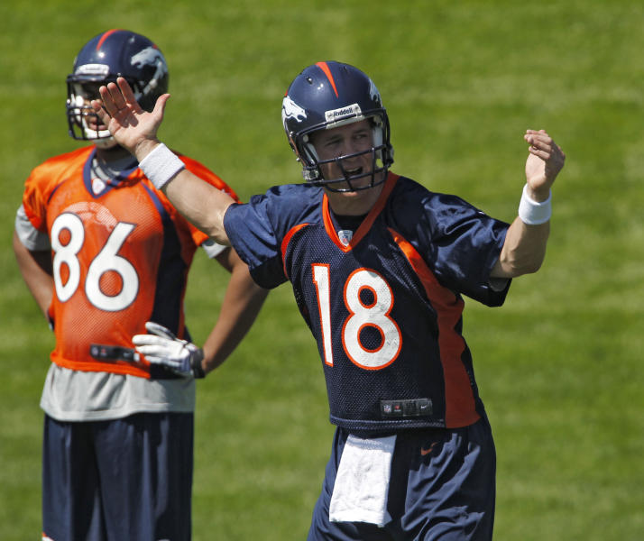 Denver Broncos quarterback Peyton Manning (18) talks to his receivers during minicamp at the NFL team's football training facility in Englewood, Colo., on Monday, May 21, 2012. At left is tight end Anthony Miller (86) (AP Photo/Ed Andrieski)