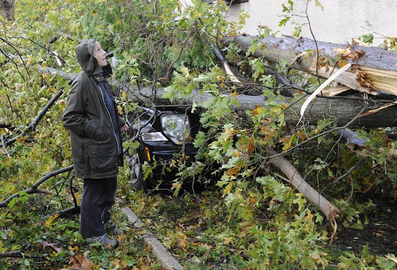 Barbara Sinenberg surveys the damage to the car and home of a neighbor, after superstorm Sandy felled trees crushing the car and bringing down power lines on Barberry Lane in Sea Cliff, N.Y. on Tuesday, Oct., 30, 2012. (AP Photo/Kathy Kmonicek)