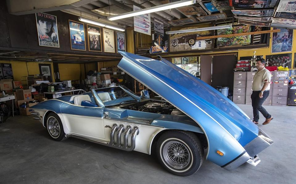 Jared Barris walks next to the Barrister, a custom coach built by the late George Barris on a 1973 Corvette chassis.