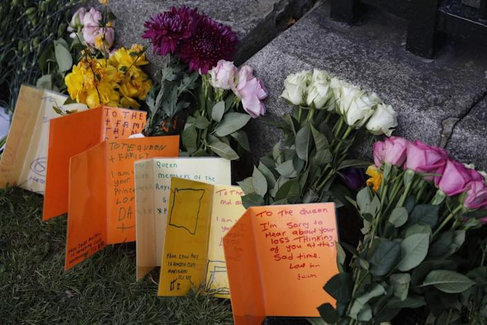 Cards written by children as a tribute to Prince Philip stand on grass amid cut flowers outside Windsor Castle