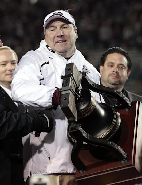 Mississippi State head coach Dan Mullen lifts the trophy after beating Rice in the Liberty Bowl NCAA college football game Tuesday, Dec. 31, 2013, in Memphis, Tenn. Mississippi State won 44-7. (AP Photo/Mark Humphrey)