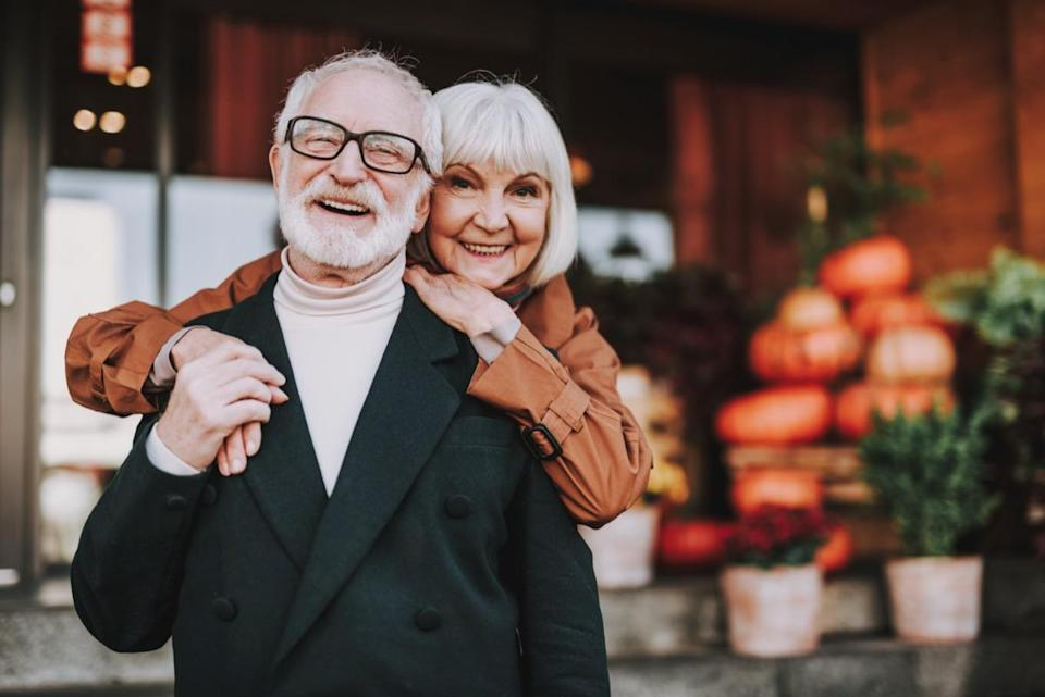 Waist up portrait of happy lady hugging husband from behind while he holding her hand. They looking at camera and smiling
