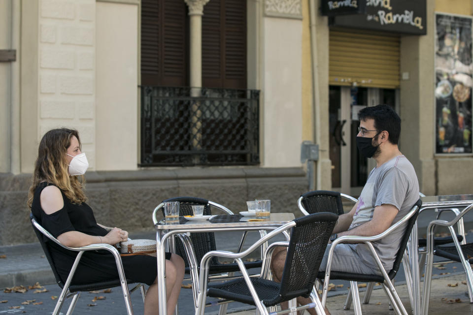 A couple talks on the terrace of a bar, wearing a mask and keeping a safe distance. Bars and restaurants should limit to 50% of their capacity, and keep the safety distance between tables, on July 17, 2020 in Hospitalet de Llobregat, Spain. (Photo by Cesc Maymo/Getty Images)