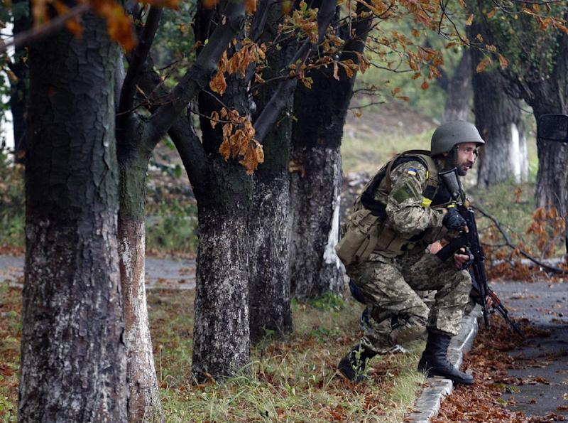 A Ukrainian serviceman bends down as he hears shooting in the small eastern city of Debaltseve, on September 9, 2014