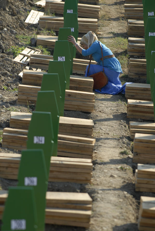 A Bosnian Muslim woman weeps near the grave of her relative among the graves of Srebrenica victims at the Memorial Cemetery in Potocari, near Srebrenica, 160 kms northeast of Sarajevo, Bosnia, Wednesday, July 11, 2012. Thousands gathered in the cemetery for the mass burial of 520 bodies, marking the 17th anniversary of the Srebrenica massacre. (AP Photo/Sulejman Omerbasic)