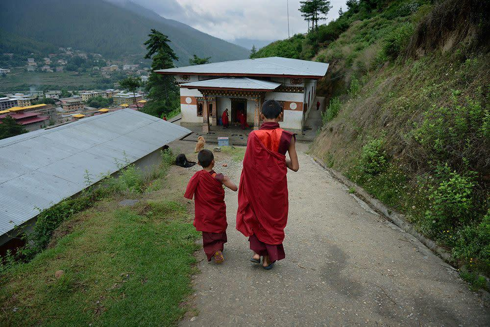 Six-year-old monk apprentice Tandi Dorji (left) speaks with an older monk as they walk to the dining hall at a monastery in Thimphu, Bhutan, on June 4, 2013.
