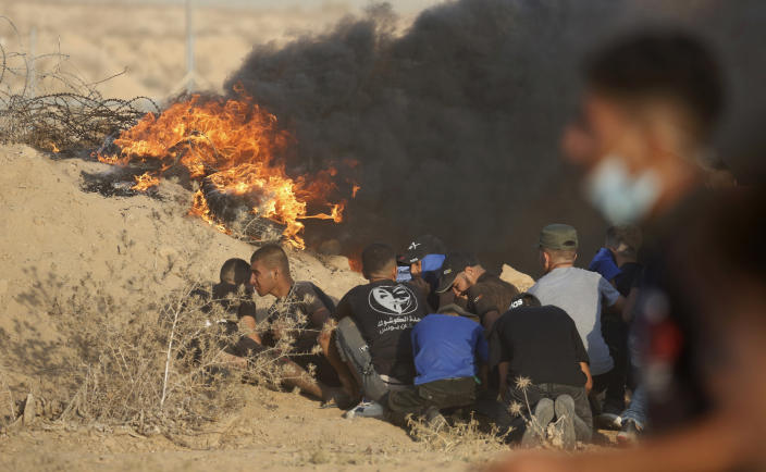 Protesters take cover next to tires on fire near the fence of Gaza Strip border with Israel during a protest east of Khan Younis, southern Gaza Strip, Wednesday, Aug. 25, 2021. Hundreds of Palestinians on Wednesday demonstrated near the Israeli border in the southern Gaza Strip, calling on Israel to ease a crippling blockade days after a similar gathering ended in deadly clashes with the Israeli army. (AP Photo/Abdel Kareem Hana)