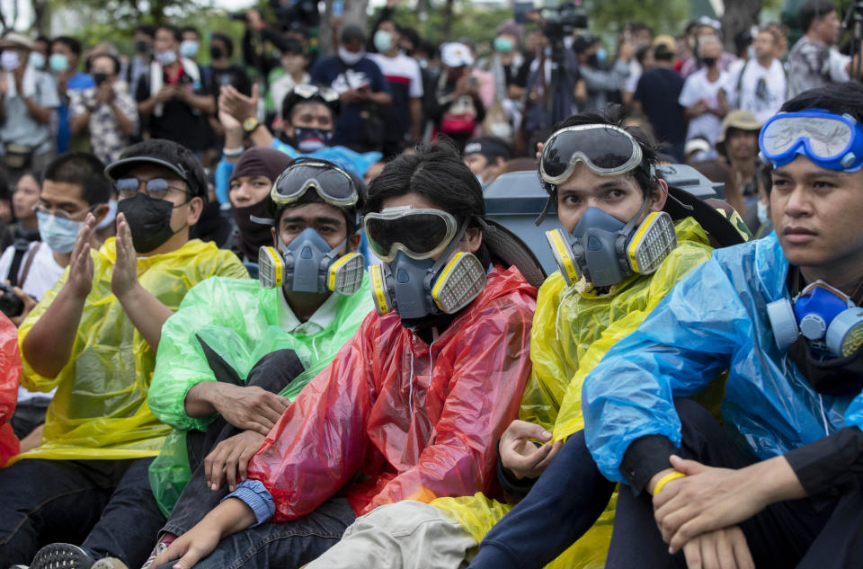 Pro-democracy protesters wearing protective masks sometimes used to avoid tear gas sit on the road during a march near Sanam Luang in Bangkok, Thailand, Sunday, Sept. 20, 2020. The mass student-led rally that began Saturday is the largest in a series of protests this year, with thousands camping overnight near the royal palace, demanding for new elections and reform of the monarchy. (AP Photo/Gemunu Amarasinghe)