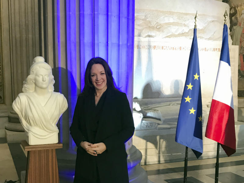 Britain's Catherine Norris Trent poses next to a bust of Marianne, left, symbol of the French Republic, and the French, right, and European flags after a naturalization ceremony in Paris' Pantheon monument, Thursday, March 21, 2019. With the looming Brexit deadline, the 38-year-old mother of two who's lived in the French capital for over a decade was one of dozens of newly-minted French nationals attending the cermony. (AP Photo/Thomas Admason)