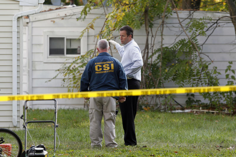 Investigators look in the rear yard of a home Tuesday, Oct. 23, 2012, in Clayton, N.J., after a body preliminarily identified as a missing 12-year-old girl's was found in a home's recycling bin. The Gloucester County Prosecutor's Office announced early Tuesday that they believed the body of Autumn Pasquale was found around 10 p.m. Monday, in a recycling bin at a home just blocks away from her house and from Borough Hall, where thousands of people gathered earlier in the evening for a tearful candlelight vigil to pray for the girl's safe return. (AP Photo/Mel Evans)