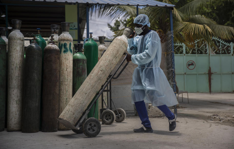 FILE - In this June 5, 2021, file photo, a hospital employee wearing protective gear transports oxygen tanks in Port-au-Prince, Haiti. In Haiti, hospitals turned away patients as the country awaits its first shipment of vaccines. Haiti received its first delivery of vaccines on July 15 after months of promises — 500,000 doses for a population over 11 million. (AP Photo/Joseph Odelyn, File)
