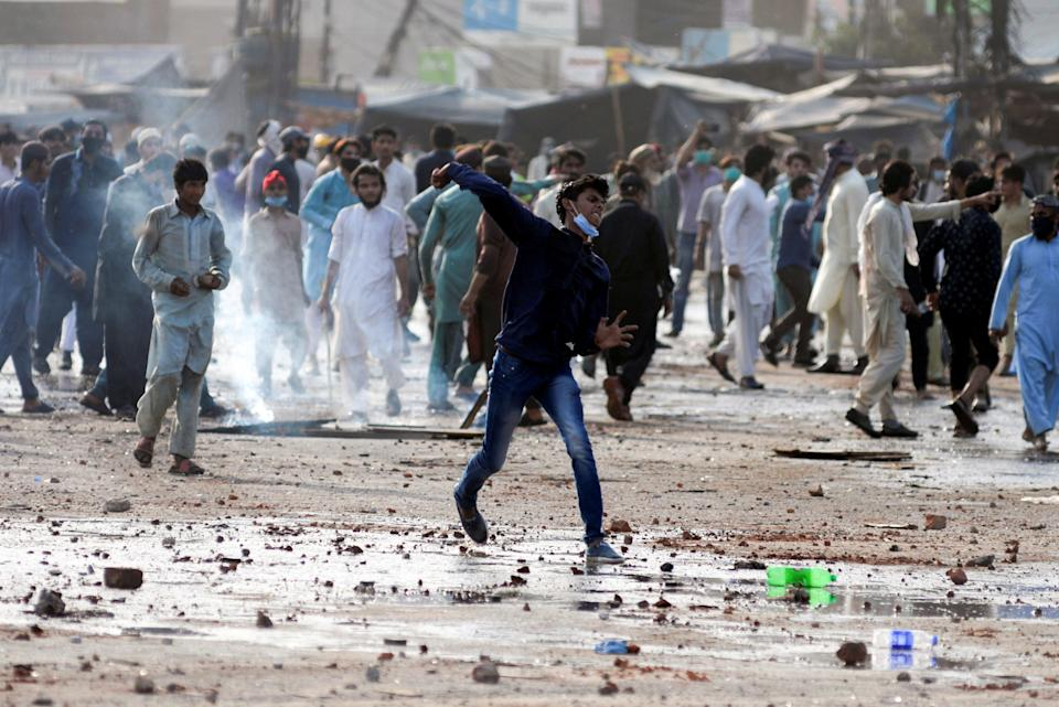 <p>An anti-French protester hurls stones towards police during a protest in Lahore, Pakistan</p> (REUTERS)