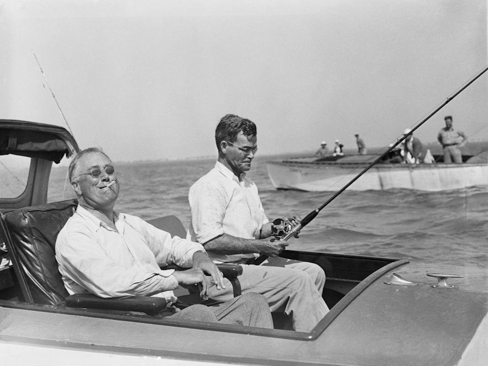 <p>Franklin D. Roosevelt smiles at the camera, while puffing on a cigarette, in 1937. The President enjoyed a day at sea as he and a companion fish for tarpon in the Gulf of Mexico. </p>