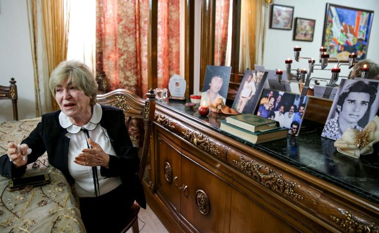 Samya Khasro, a woman from Iraq's once-persecuted Shiite Kurdish minority, sits next to pictures of family members who vanished 35 years prior and whose whereabouts remain unknown (AFP Photo/SABAH ARAR)