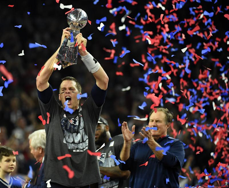 Tom Brady #12 of the New England Patriots holds the Vince Lombardi Trophy as Head coach Bill Belichick (R) looks on after defeating the Atlanta Falcons 34-28 in overtime during Super Bowl 51 at NRG Stadium on February 5, 2017 in Houston, Texas. The Patriots defeated the Falcons 34-28 after overtime. / AFP / Timothy A. CLARY (Photo credit should read TIMOTHY A. CLARY/AFP via Getty Images)