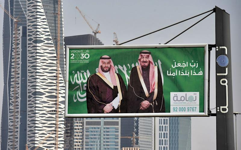 Portraits of Saudi King Salman (R) and his son Crown Prince Mohammed bin Salman on display in Riyadh as the city prepares for a major investment conference - AFP