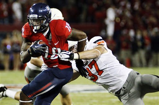 Arizona wide receiver Terrence Miller (18) runs against Oklahoma State linebacker Alex Elkins (37) during the first half of an NCAA college football game at Arizona Stadium in Tucson, Ariz., Saturday, Sept. 8, 2012. (AP Photo/Wily Low)