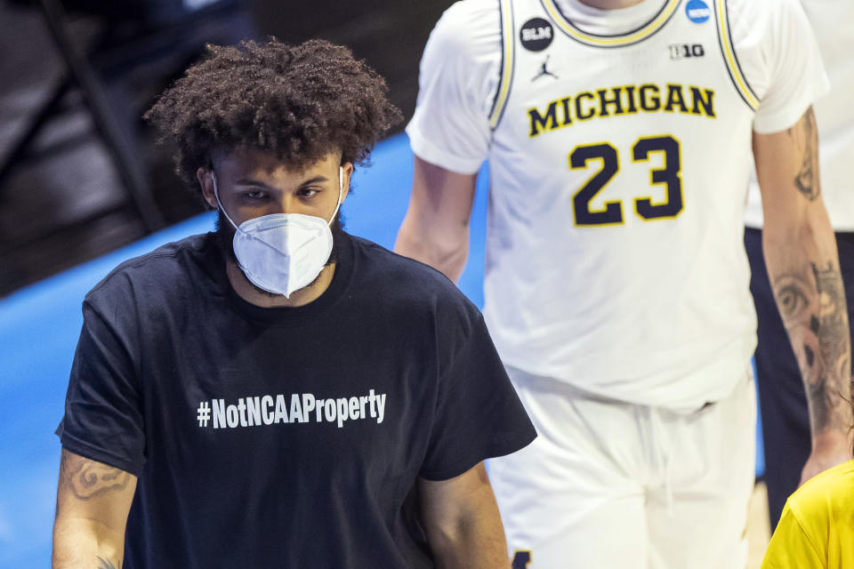 """Michigan's Isaiah Livers wears a T-shirt that reads """"#NotNCAAProperty"""" as he walks off the court with teammates after the first half of a first-round game against Texas Southern in the NCAA men's college basketball tournament, Saturday, March 20, 2021, at Mackey Arena in West Lafayette, Ind. (AP Photo/Robert Franklin)"""
