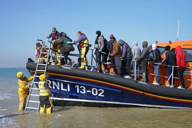 A group of people thought to be migrants are brought ashore from the local lifeboat at Dungeness in Kent